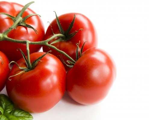 Cluster of five tomatoes on a white background with basil.