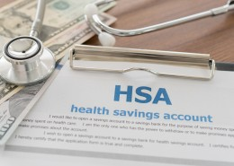 health savings account HSA concept with application form,dollar money, stethoscope on desk.